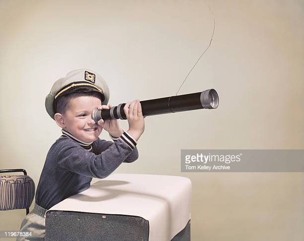 Boy wearing sailor hat looking through telescope, smiling