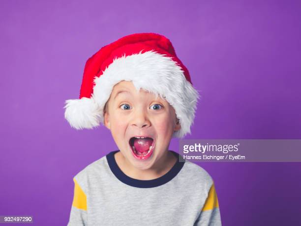 boy wearing santa hat against purple background - santa hat stock photos and pictures
