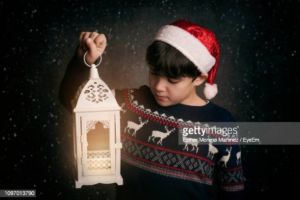 boy wearing santa hat holding illuminated lantern while standing outdoors during snowfall at night - christmas decore candle stock pictures, royalty-free photos & images