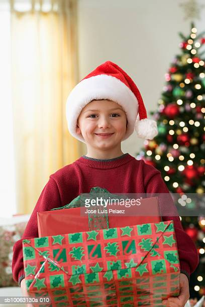 boy (6-7 years) wearing santa hat holding present in living room, portrait - 6 7 years stock pictures, royalty-free photos & images