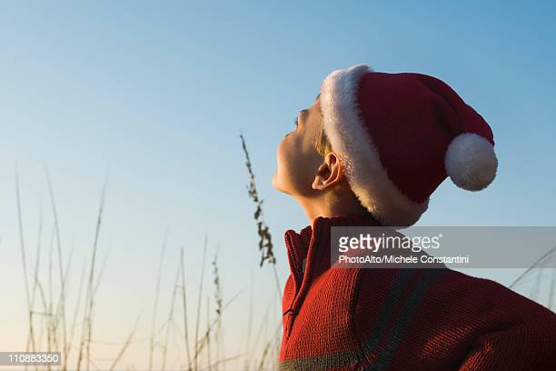 Boy wearing Santa hat outdoors, contemplatively looking away