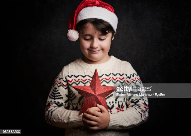 boy wearing santa hat while holding star shape decoration against black background - jersey de cuello alto fotografías e imágenes de stock