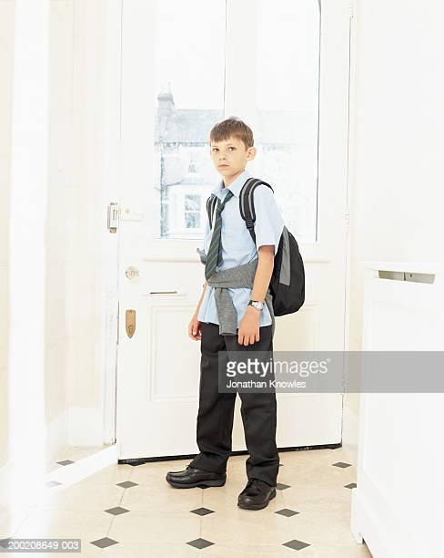 Boy (8-10) wearing school uniform and rucksack, standing by front door
