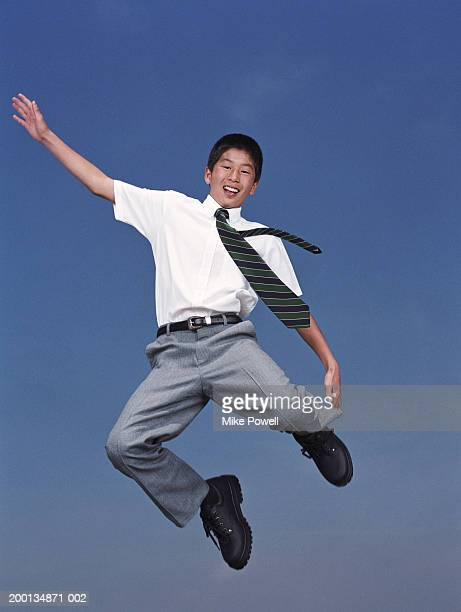 Boy (12-14) wearing school uniform, jumping in air, portrait
