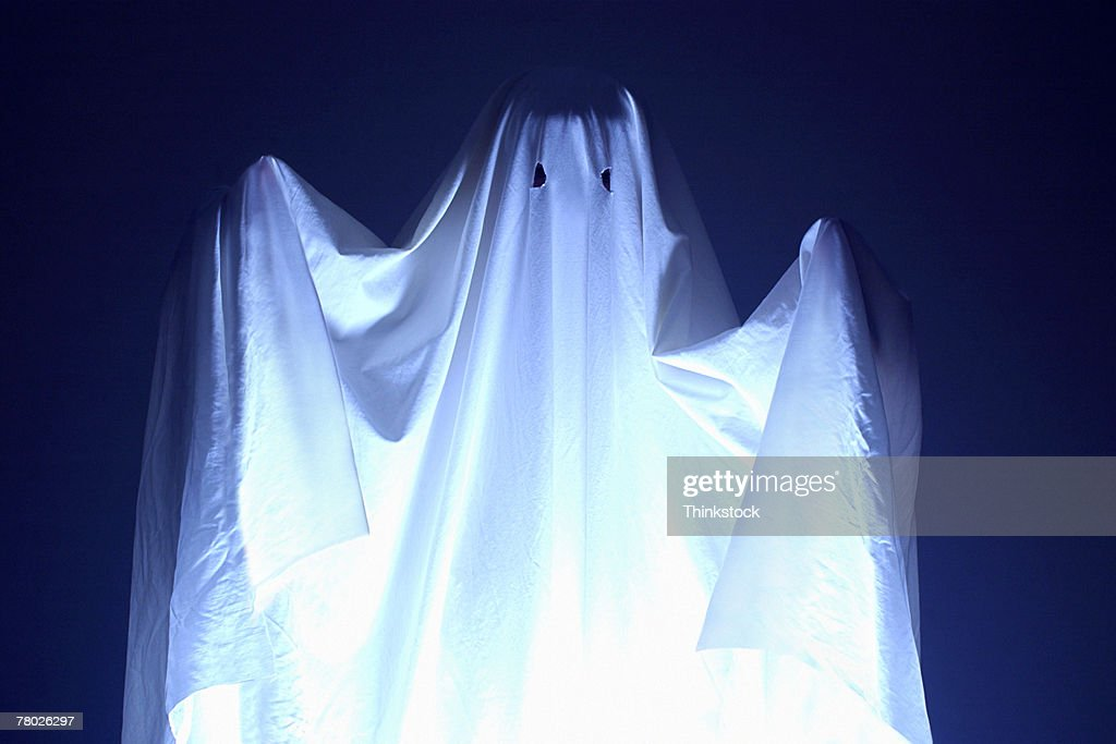 Boy wearing sheet for Halloween ghost costume; he is also holding a spooky doll. : Stock Photo