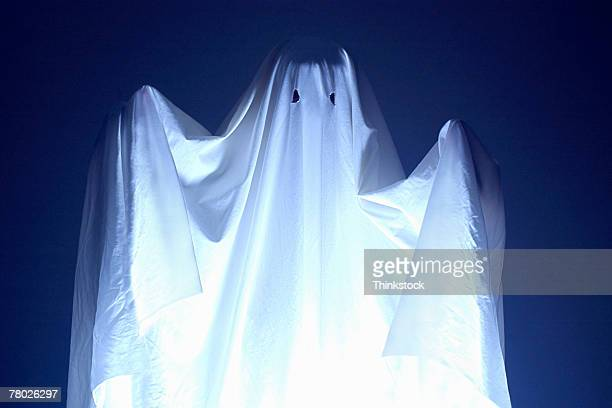 Boy wearing sheet for Halloween ghost costume; he is also holding a spooky doll.