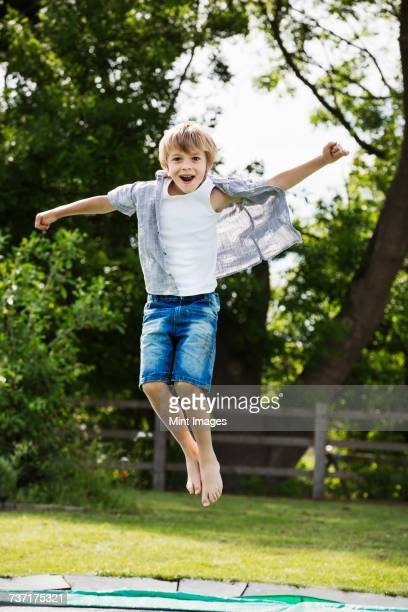 Boy wearing shirt and denim shorts jumping on a trampoline in a garden.