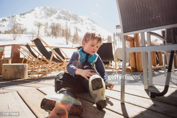 Boy wearing ski boots by seat on floorboard
