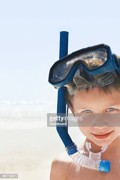 Boy (7-9) wearing snorkel and mask at beach portrait