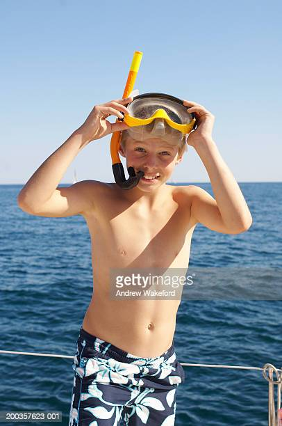 Boy (10-11 years) wearing snorkel and mask standing on yacht, smiling