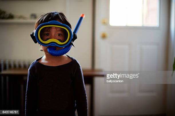 boy wearing snorkel in living room - scuba mask stock pictures, royalty-free photos & images