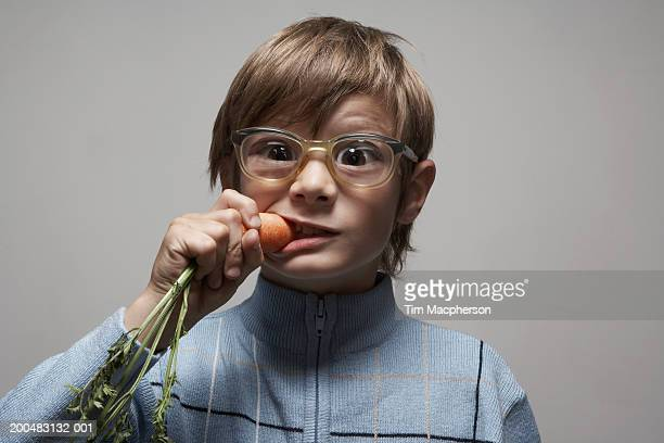 Boy (8-10) wearing spectacles biting carrot, portrait