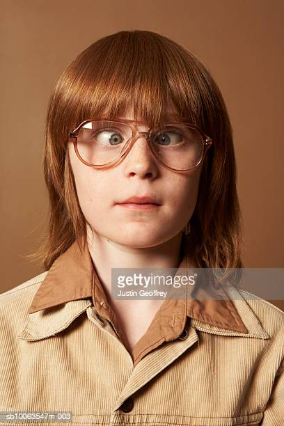 Boy (8-10) wearing spectacles crossing eyes, close-up