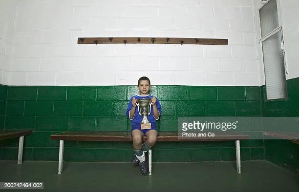 Boy (9-11) wearing sports uniform in change room, holding trophy