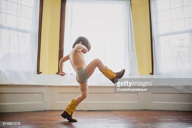 Boy wearing stomping around indoors in cowboy boots