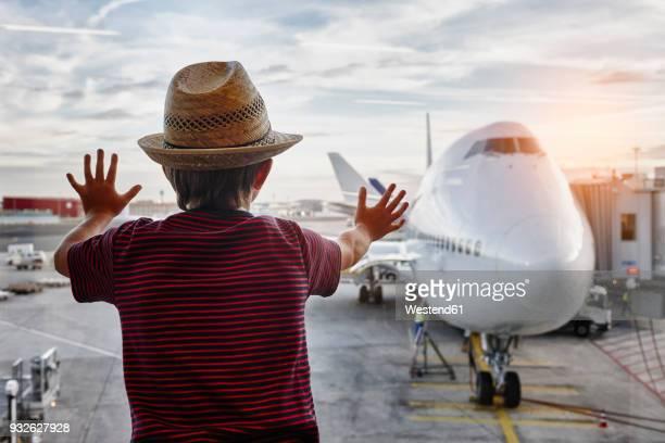 boy wearing straw hat looking through window to airplane on the apron - nur jungen stock-fotos und bilder