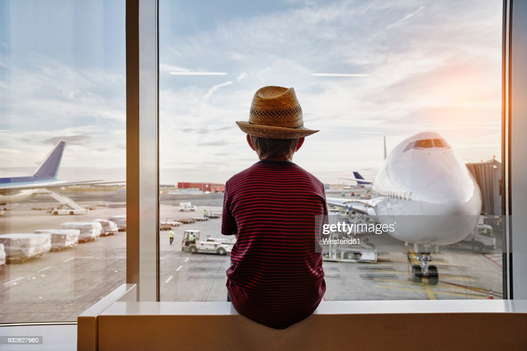 Boy wearing straw hat looking through window to airplane on the apron : Stock-Foto
