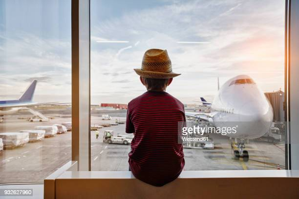 boy wearing straw hat looking through window to airplane on the apron - volare foto e immagini stock