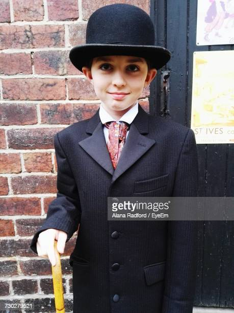 Boy Wearing Suit And Hat Standing Against Wall
