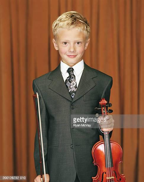 Boy (8-10) wearing suit, holding violin, portrait
