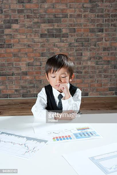 Boy wearing suit looking over documents