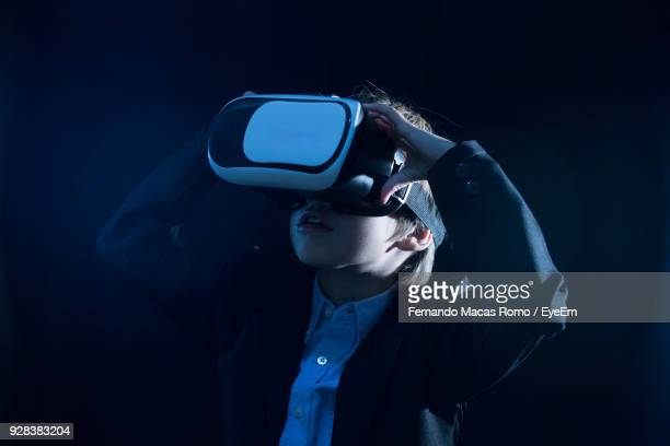 boy wearing suit while using virtual reality simulator - virtual reality simulator stock photos and pictures