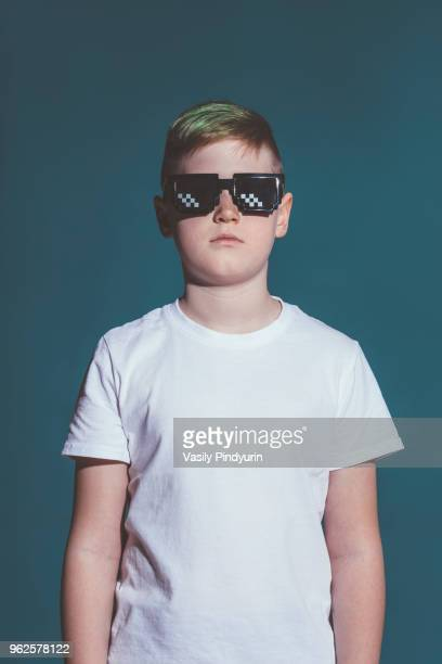 boy wearing sunglasses against gray background - innocence stock pictures, royalty-free photos & images