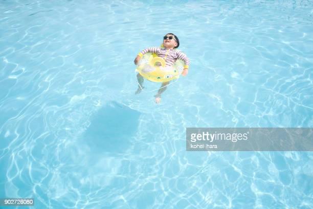 プールで遊んでサングラスを身に着けている男の子