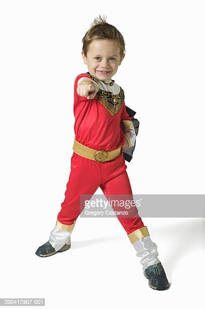 Boy (3-5) wearing superhero costume, thrusting arm forward