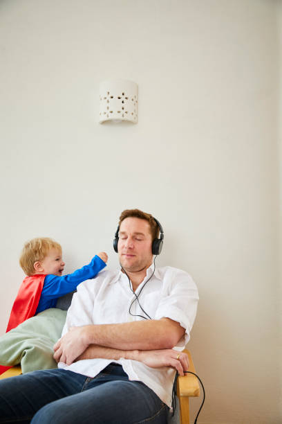 Boy wearing superman costume and annoying father while listeining to music with headphones