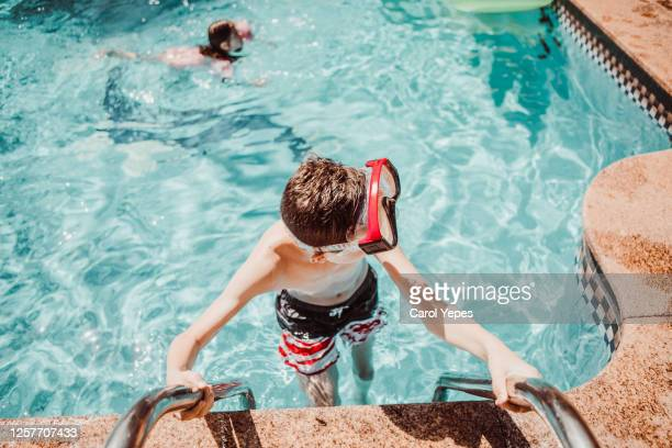 boy wearing swim googles at pool during holidays - google stock pictures, royalty-free photos & images