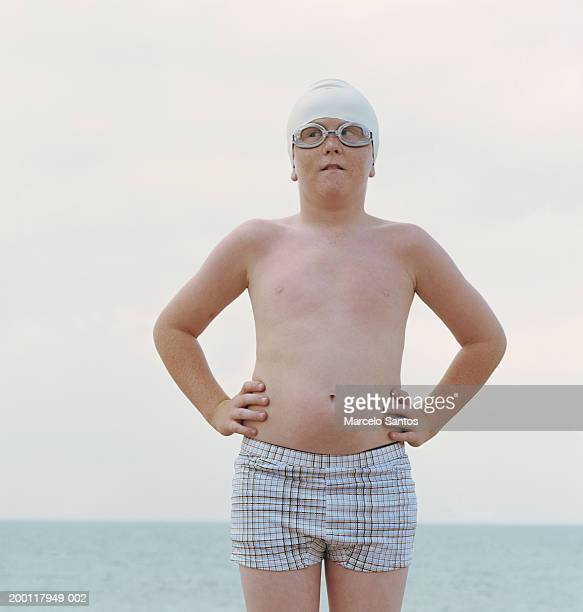 boy (10-12) wearing swimming cap and goggles, hands on hips - chubby boy stock photos and pictures