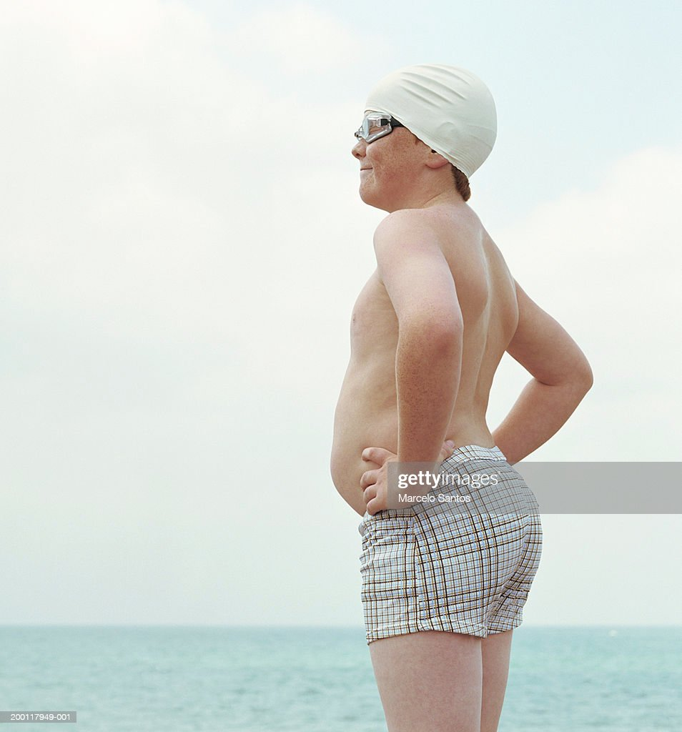 Boy (10-12) wearing swimming cap and goggles, hands on hips, side view : Stock Photo