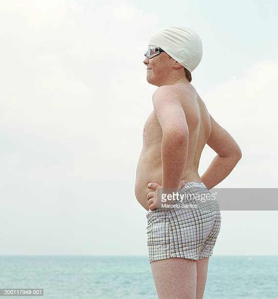 Boy (10-12) wearing swimming cap and goggles, hands on hips, side view