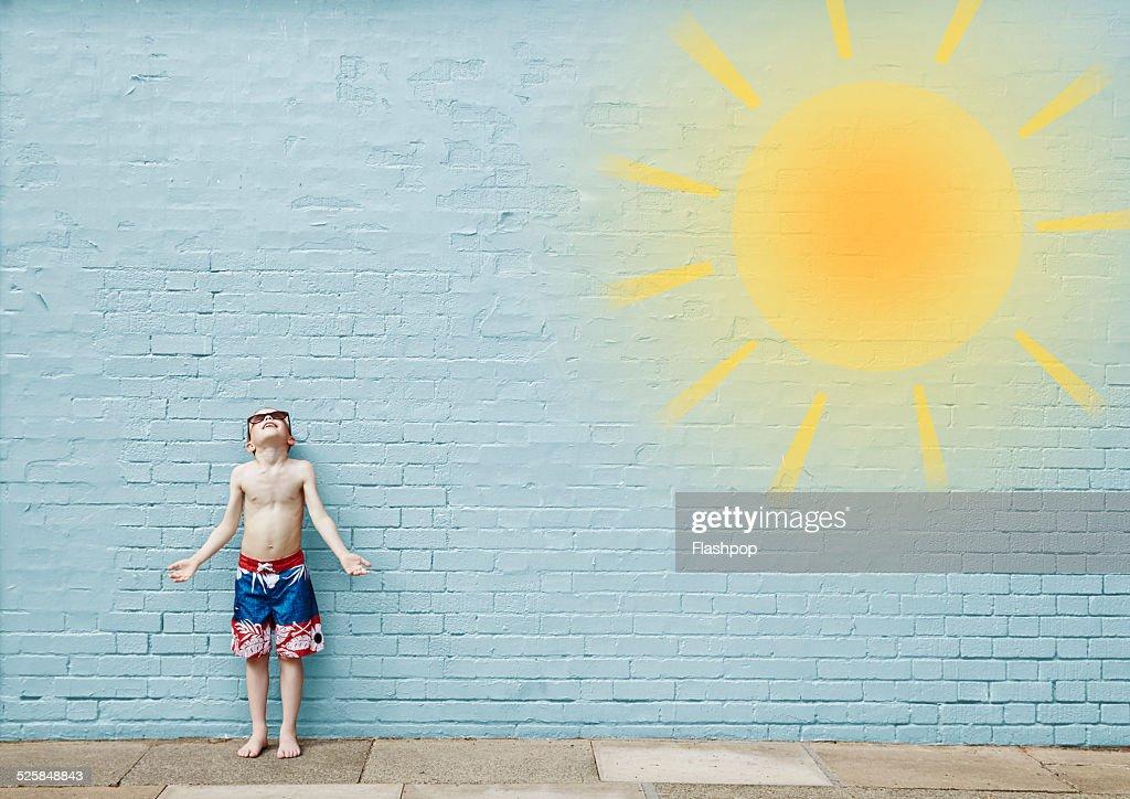 Boy wearing swimming shorts. Cartoon of sun : Stock Photo