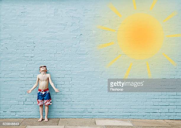 Boy wearing swimming shorts. Cartoon of sun