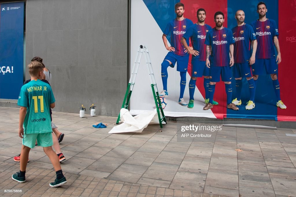 TOPSHOT - A boy wearing the jersey of Barcelona's Brazilian forward Neymar walks past a new poster being put up outside the Camp Nou Stadium in Barcelona on August 2, 2017. The previous poster featured Barcelona's Brazilian forward Neymar. Neymar could be presented as a Paris Saint-Germain player as early as this weekend for a world record fee as Barcelona admitted defeat in convincing the Brazilian to stay at the Camp Nou on August 2. / AFP PHOTO / Josep LAGO