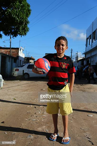 Boy wearing the shirt of Recife football team Sport Club do Recife located in the state of Pernambuco holding his football in Rua Realengo