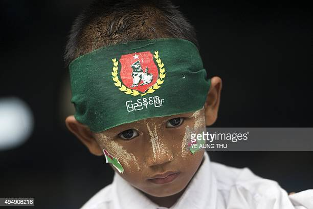 A boy wearing the traditional sun protection thanaka facial paste and stickers of the armybacked ruling Union Solidarity and Development Party looks...