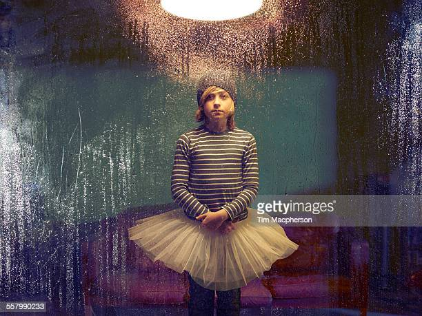 Boy wearing Tutu stands by window