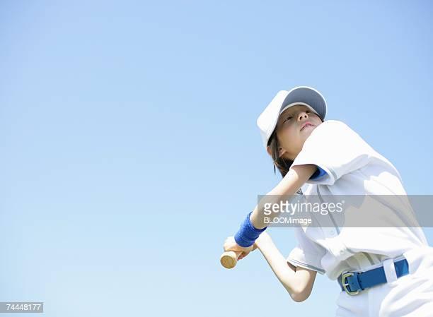 boy wearing uniform of baseball hitting ball with bat - sports uniform ストックフォトと画像