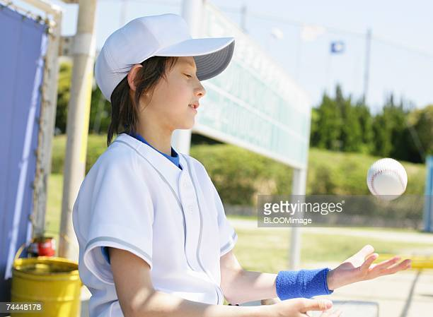 boy wearing uniform of baseball throwing ball with sitting on bench - 野球帽 ストックフォトと画像