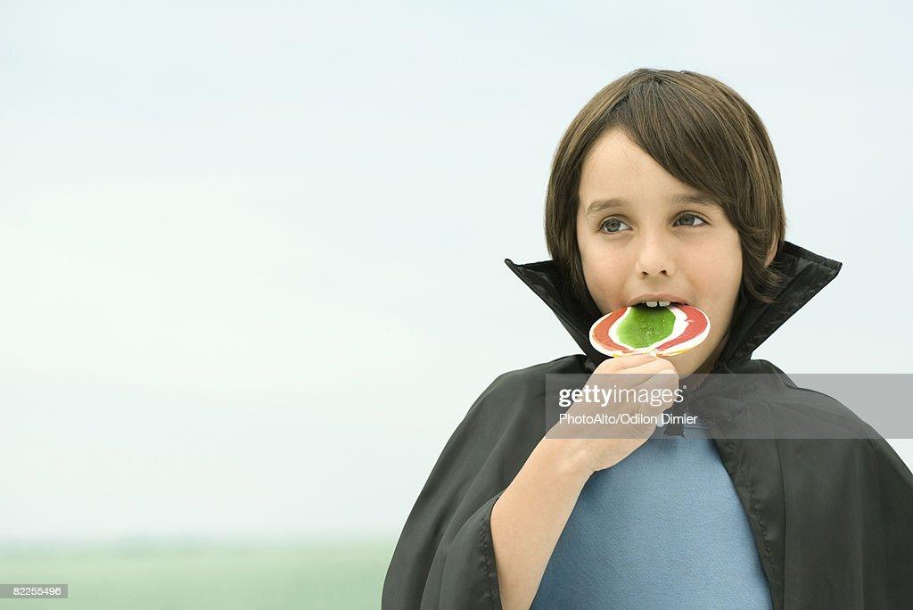 Boy wearing vampire cape, eating large lollipop, portrait : Stock Photo
