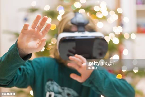 boy wearing virtual reality glasses in front of a christmas tree