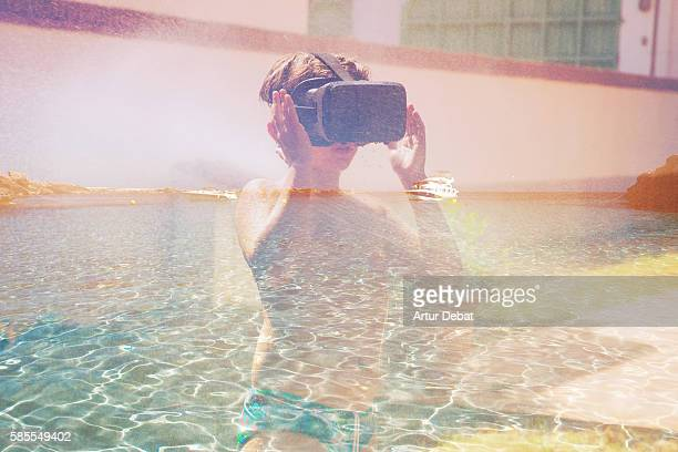 Boy wearing virtual reality headset cooling off on summer in the backyard home transported to a paradise beach in the Mediterranean sea with clear water.