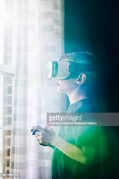 Boy wearing virtual reality headset holding controller