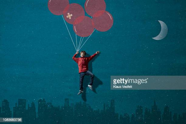 Boy wearing VR goggles holding painted imaginary balloons flying above skyline