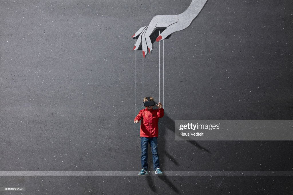 Boy wearing VR goggles laying on background with imaginary painted puppeteer hand : Stock Photo