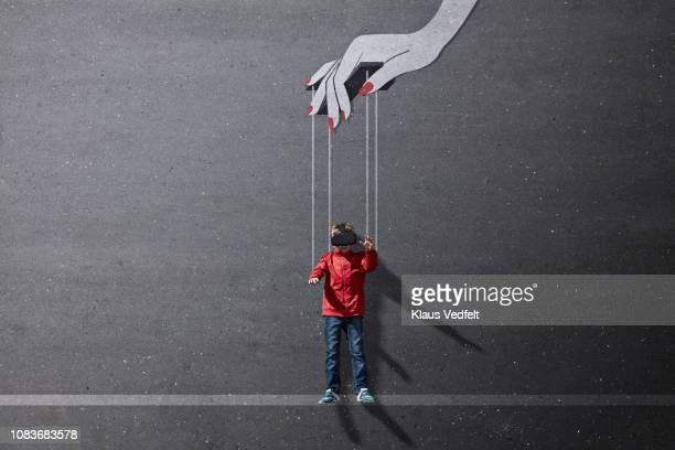 Boy wearing VR goggles laying on background with imaginary painted puppeteer hand
