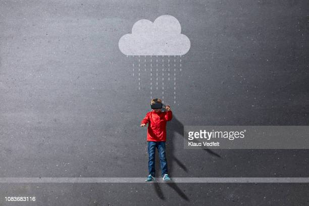 Boy wearing VR goggles standing under imaginary painted rain cloud